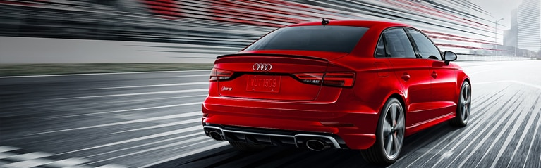 Rear-view of the Audi RS 3 Sedan driving on the track.