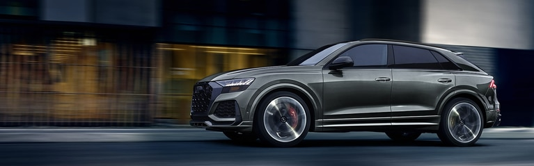 Three-quarter front profile of Audi RS Q8 driving on the road.